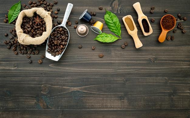 コーヒー豆のコーヒーカプセルと暗い木製のテーブルの上のコーヒーの粉。