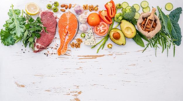 白い木製の背景に健康食品の選択のための原料。