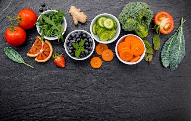 カラフルな健康的なスムージーと新鮮なトロピカルフルーツとコピースペースと暗い石の背景にスーパーフードの瓶の中のジュース。