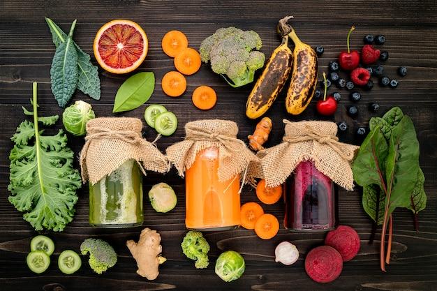 カラフルな健康的なスムージーと新鮮なトロピカルフルーツと木製の背景にスーパーフードの瓶の中のジュース。