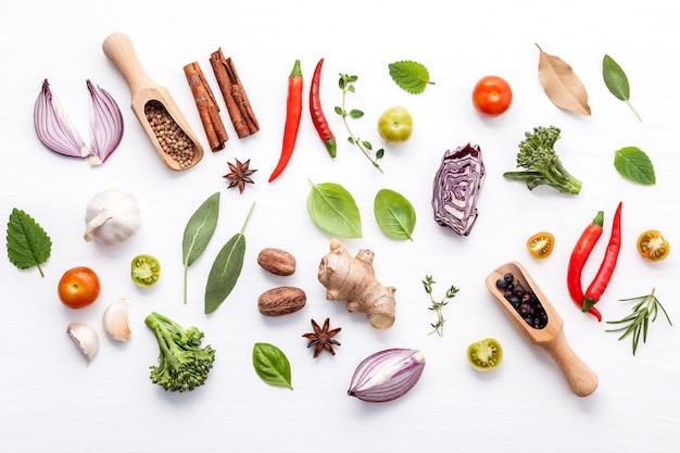 白い背景に様々な新鮮な野菜やハーブ