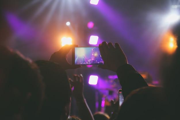 写真を撮るまたはコンサートステージのビデオを記録するスマートフォンを手に持つ