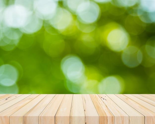製品表示のための抽象的な自然な緑のぼけボケ背景を持つ古い木の板