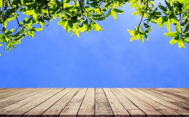 製品表示のための抽象的な自然な緑の葉の背景を持つ木の板