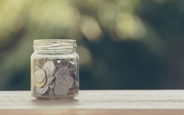 節約と金融投資の概念のためのガラスの瓶にお金コイン