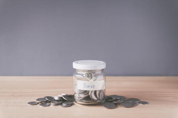 コインと木製の机の上のガラスの瓶にコインのスタック、お金の概念を保存