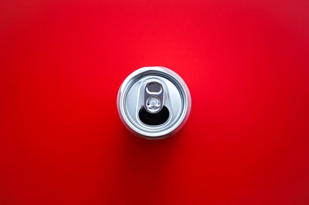 Плоская прокладка из алюминиевой банки открыта на красном фоне