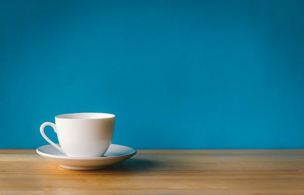 青い背景の木製の机の上の白いコーヒーカップ