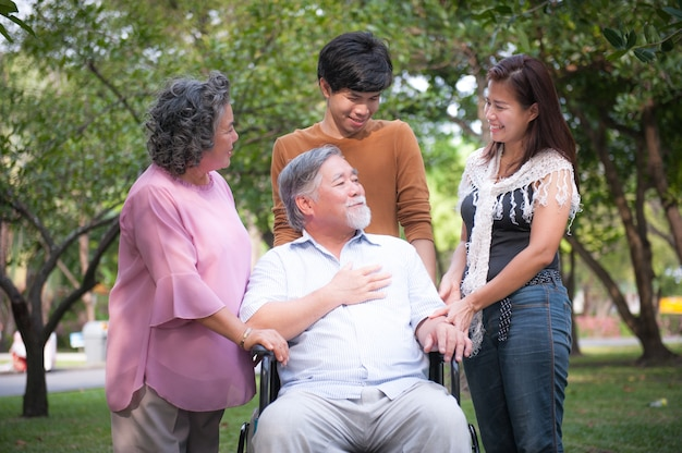 彼の幸せな家族を歓迎する車椅子の陽気な障害者の祖父。