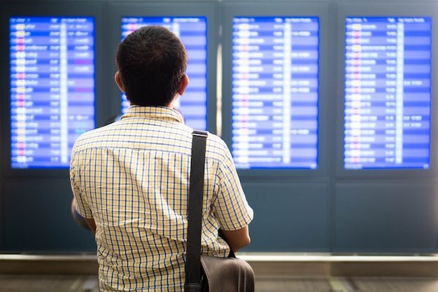Пассажир смотрит на расписание борту в аэропорту.