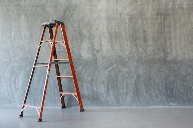 裸のセメントの壁にオレンジ色の鉄のはしご