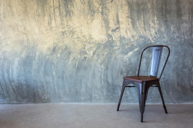 裸のセメントの壁の椅子