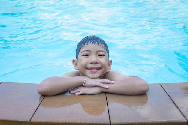アジアの少年青のスイミングプールの境界線に笑みを浮かべて