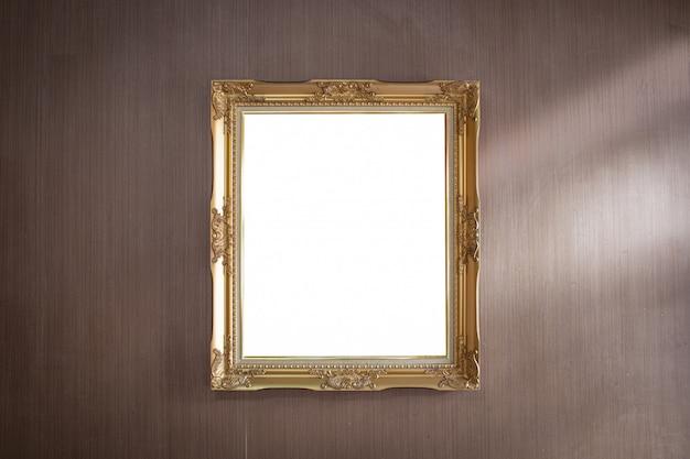 Золотая рамка на темной деревянной стене