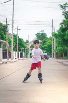 アジアの少年はローラーブレードをしている