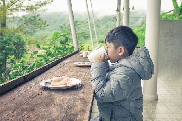 パーカーのアジアの子供は、牛乳と朝食を飲むためにグラスを上げています