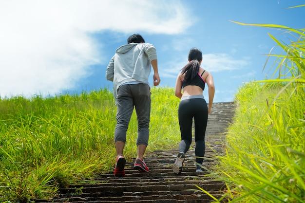 森林のトレイルで二階で走っている運動カップル