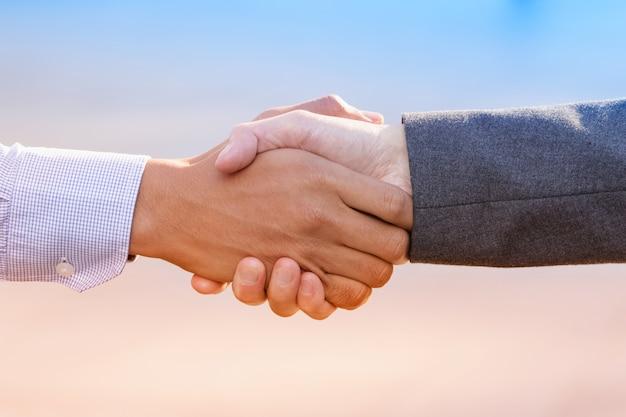 信頼できるパートナーシップのために立っているビジネス人々の握手の拡大