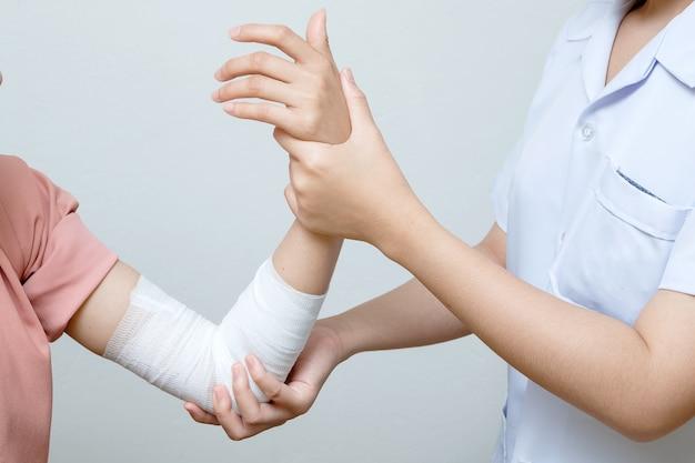 Медсестра, применяющая повязку больному раненному локту