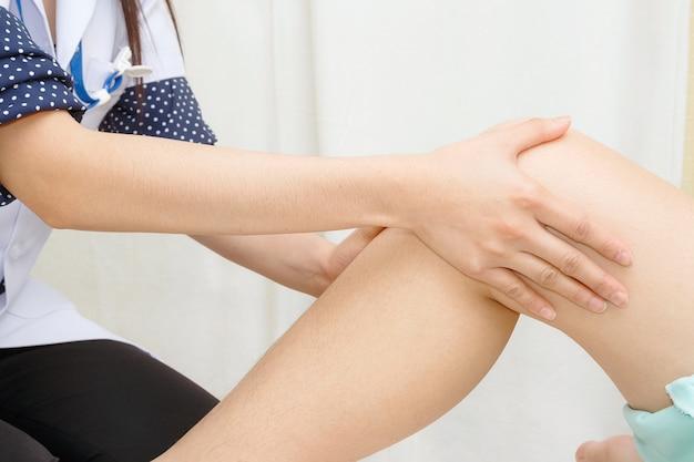 医師は患者の膝を検査する