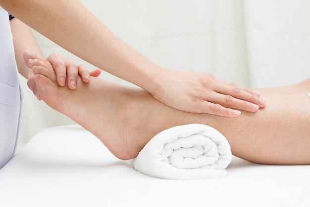 足のマッサージ、女性の足をマッサージするセラピストの手