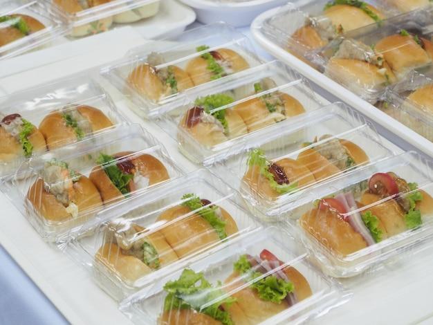 会議の休憩のために、パン、サラダおよび豚肉をプラスチックの箱に詰め込む。