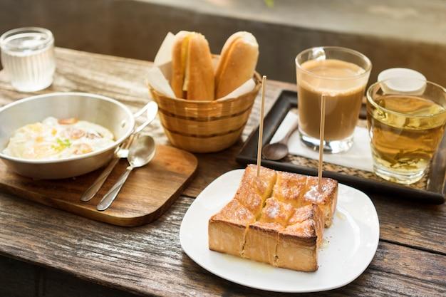 Набор для завтрака, хлеб, горячий кофе, яичный омлет и горячий чай на деревянном столе, естественное освещение