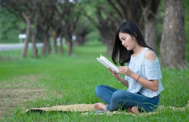 アジアの女性は公園で読書に座る