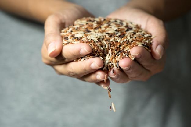 Крупным планом зерновых рисовых зерен, падающих из женской руки
