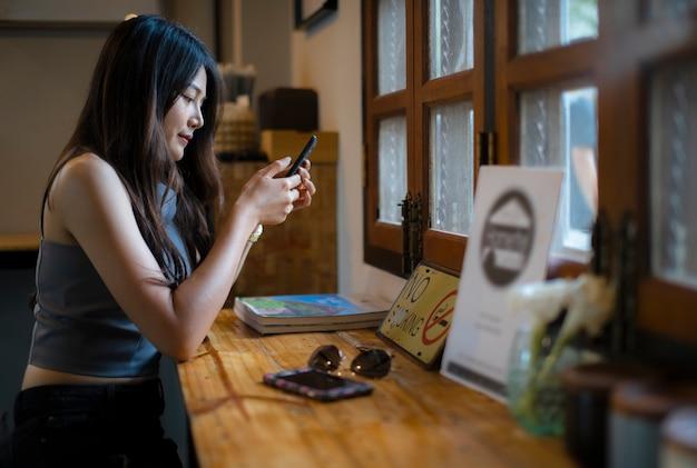 アジアの女性がコーヒーショップで携帯電話の情報を確認する