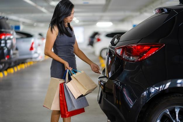 アジアの女性は車の後部に買い物袋を置いています