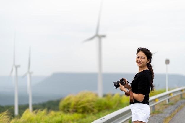 アジアの女性は風車や草原を写真撮影できてとても嬉しいです