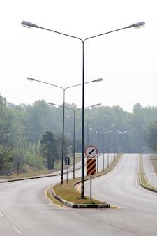 Дорога и знак с уличными фонарями