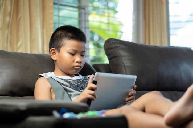 アジアの少年はゲームをプレイしたり、デジタルタプレットやソファのリビングルームでスマートフォンで漫画を見てします。