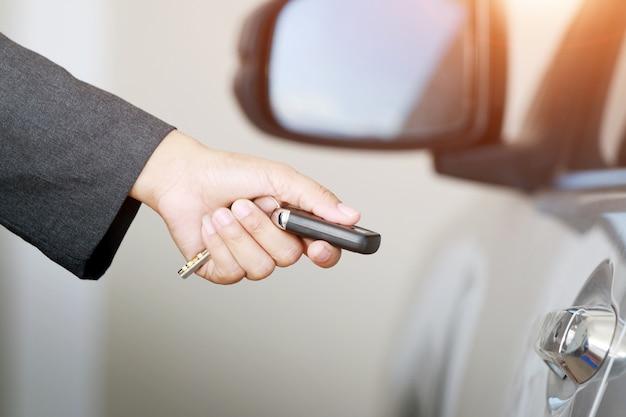 ビジネスウーマンは、リモートの車のキーを表示します