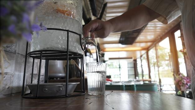 Человек наливает холодную воду из резервуара в стакан