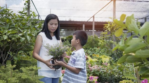 Азиатские мать и сын заботятся о деревьях в саду.