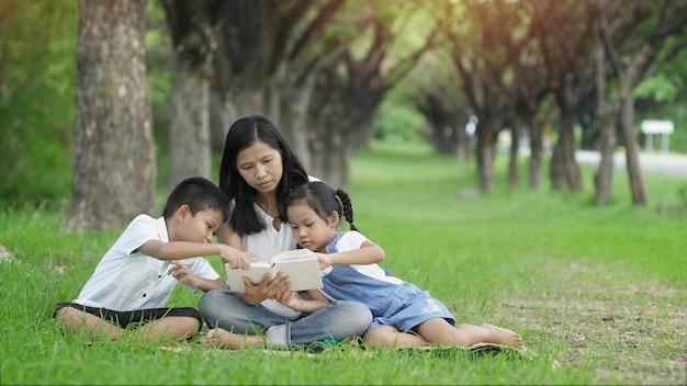 幸せな家族、母娘と息子が庭で本を読んで活動を共同します。