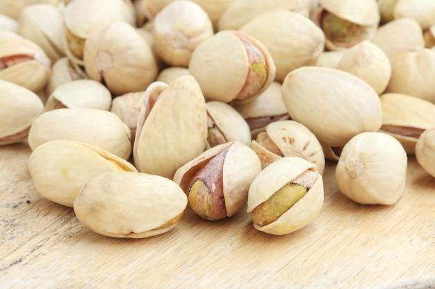 木材の背景にピスタチオナッツ。