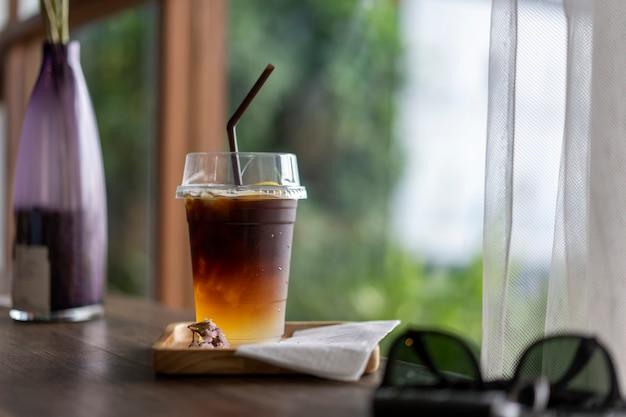 木製のテーブルの上に置かれた冷たいブラックコーヒードリンク