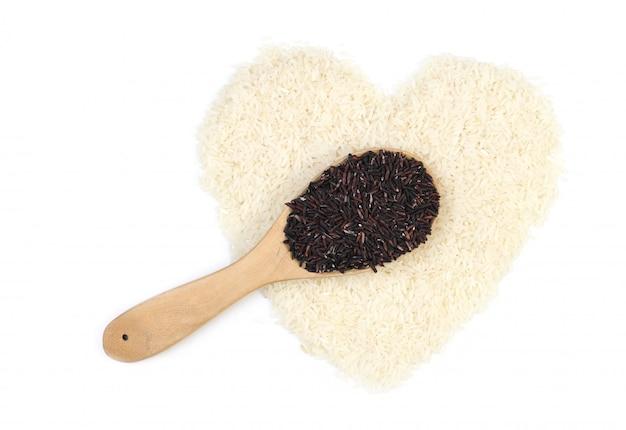 Ложка черного риса (похоронный рис) и жасминовый рис в форме сердца, изолированные на белом фоне.
