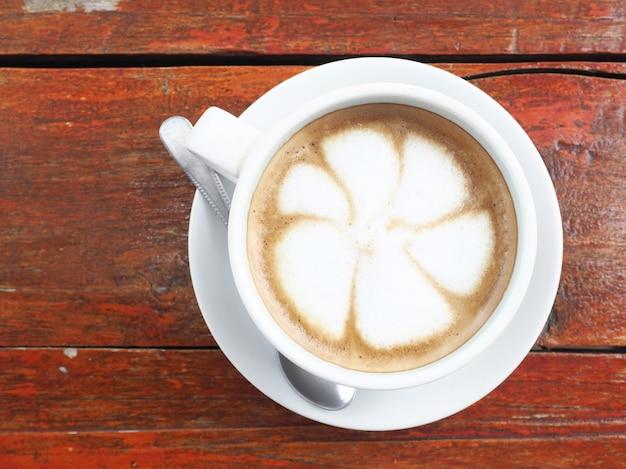 白いカップで熱いラテコーヒー。上からの眺め。