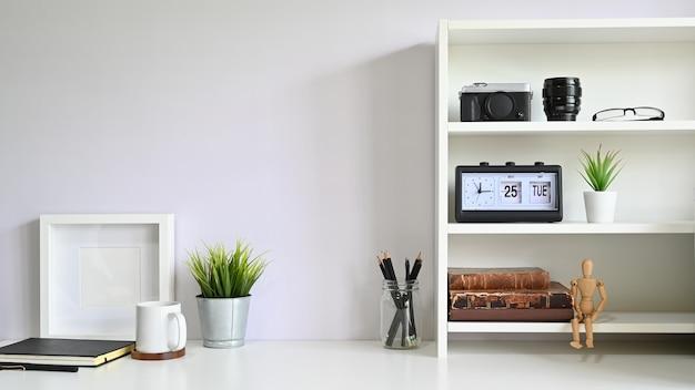 Рабочее пространство полки с камерой, объектив с фоторамкой и кружка кофе на столе.