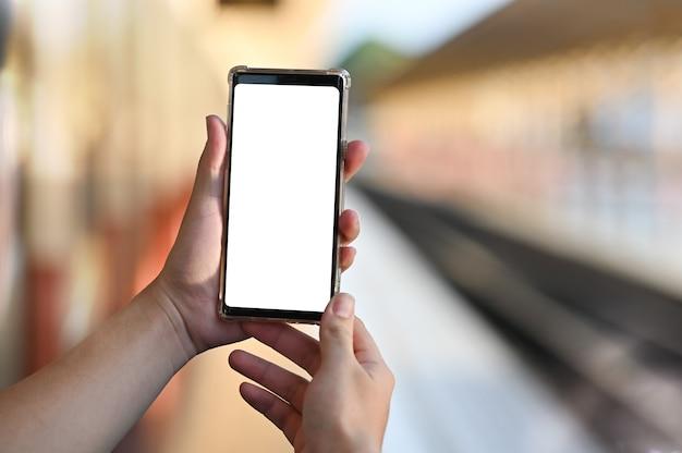 男の手は屋外の視点でモックアップスマートフォンを保持しています。