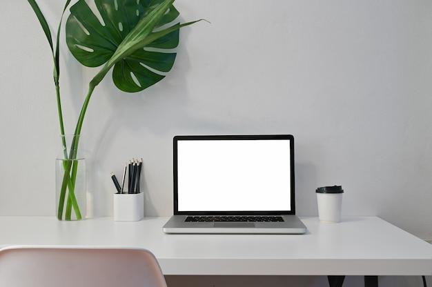 ワークスペースコンピューターとモックアップのラップトップコンピューター、コーヒー、鉛筆、植物の装飾。