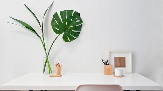 ワークスペースの創造的なデスクフォトフレーム、コーヒー、植物の装飾が施された鉛筆。