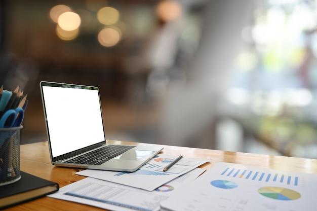 空の画面を持つビジネステーブルの上のモックアップのラップトップコンピューター。