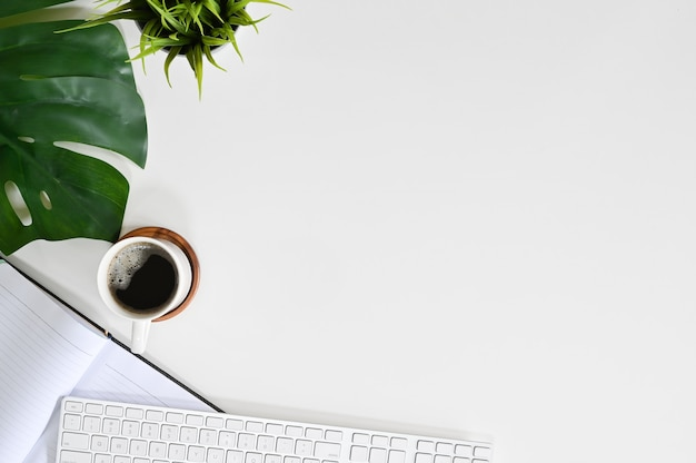 オフィスデスクコンピューターのキーボード、コーヒー、植物の装飾、ノートブックトップビューコピースペース。