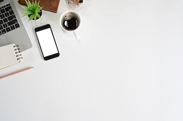 オフィスの机の上のスマートフォン、ラップトップ、コーヒー、本、メモ帳のコピースペース