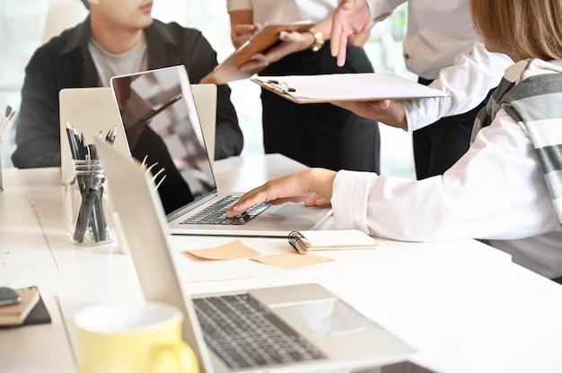 スタートアップビジネスのオンラインマーケティングチームは、トリミングされたショットでラップトップおよびドキュメントペーパーと会議します。